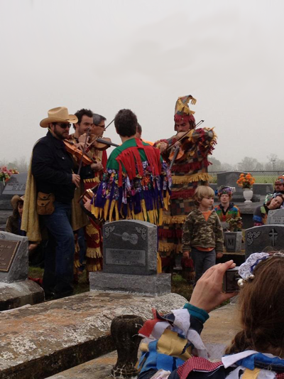 Steve Riley, Joel Savoy, and Wilson Savoy play at the grave of Dennis McGee during Cajun Mardi Gras